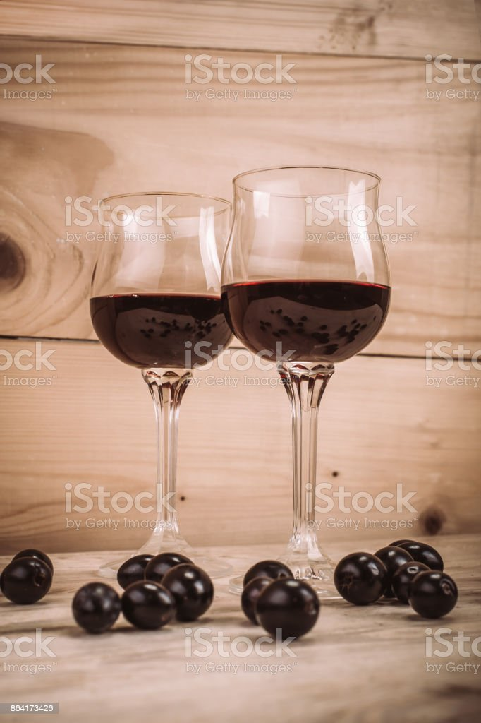 Two glasses of red wine and grapes on wooden table royalty-free stock photo