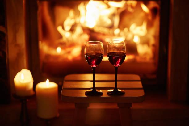 i̇ki bardak kırmızı şarap şömine yakın - romantiklik stok fotoğraflar ve resimler