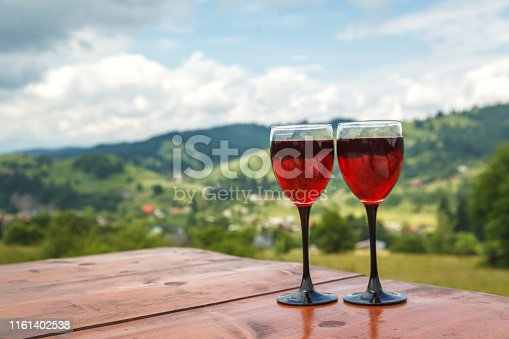 Two glasses of red wine on the background of the mountains, Ukraine, the Carpathian mountains.