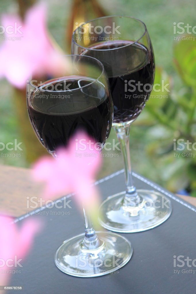 two glasses of red wine on the wooden deck stock photo