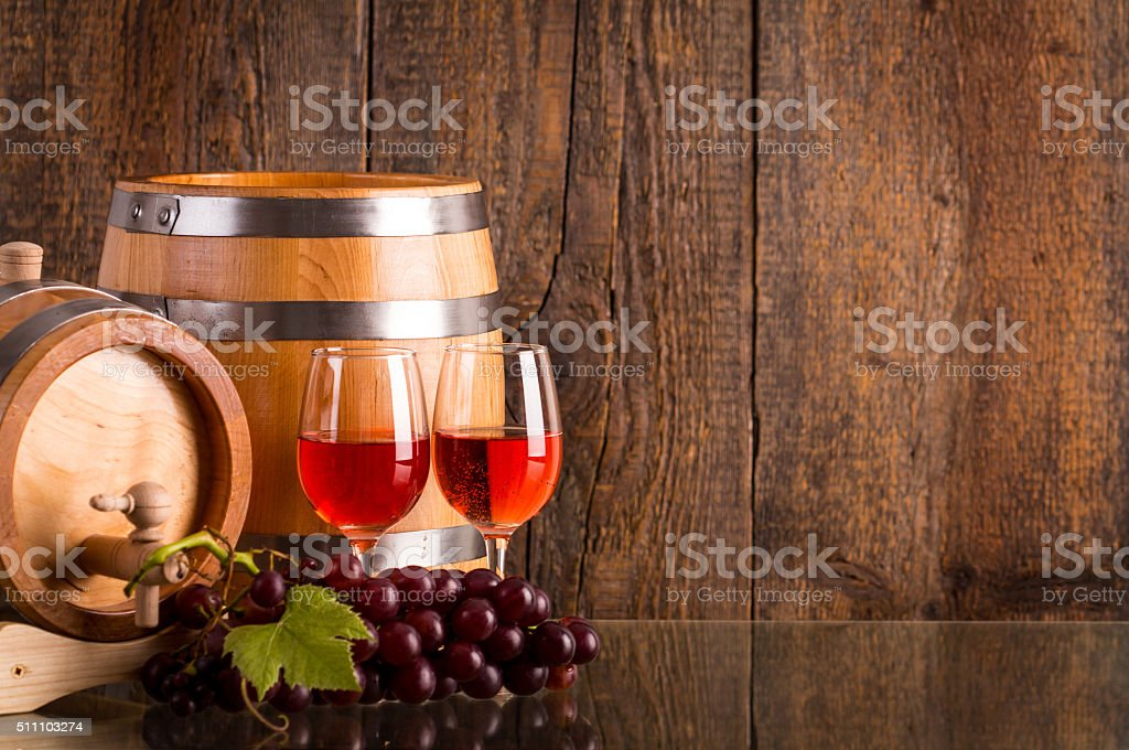 Two glasses of rosé wine with two barrels and grapes stock photo