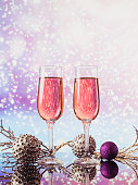 istock Two glasses of rose champagne and Christmas or New Year decoration with a golden light bokeh on background. Romantic dinner. Winter holiday concept. 1301200196