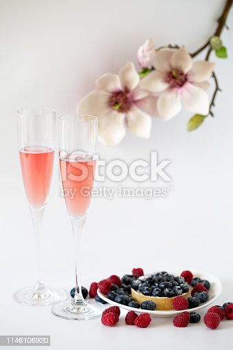 Two glasses of rose sparking wine with berries and flowers on white background