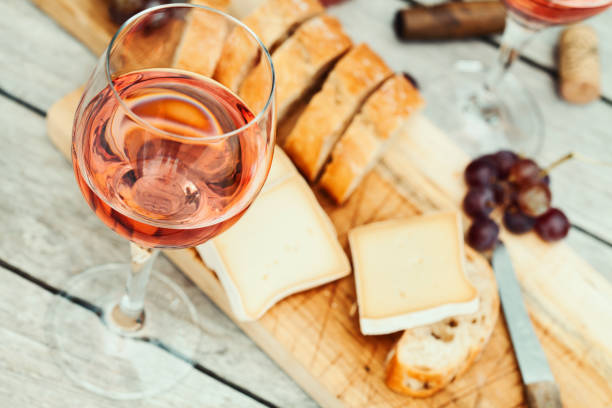 Two glasses of rose wine and board with fruits, bread and cheese on wooden table stock photo