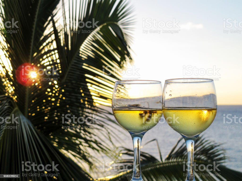 Sunset lights up two glasses of sparkling white wine on a balcony...