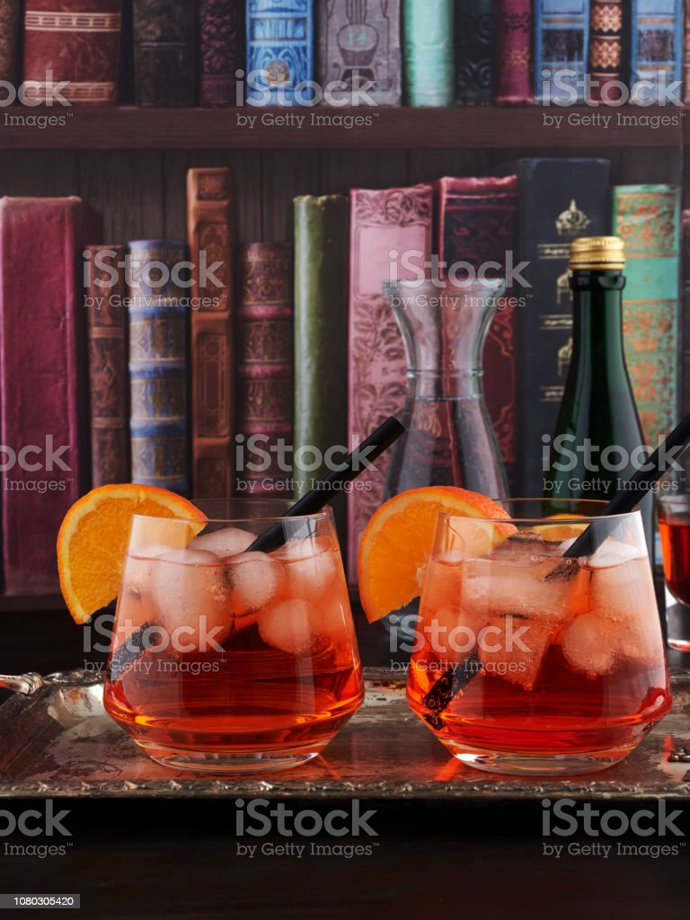 Two glasses of Aperol Spritz set on a silver tray, with a bookshelf wallpaper background stock photo