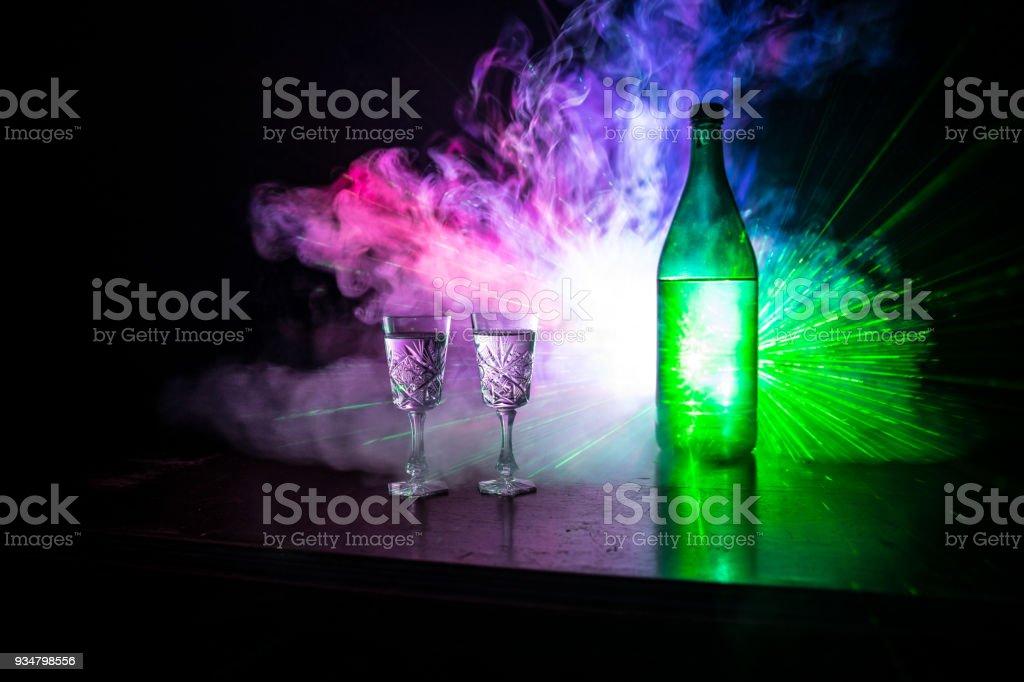 짙은 안개에 병 보드카 2 잔 클럽 빛나는 빛 (레이저, Stobe) 멀티 컬러와 스타일 배경. 클럽 테마 장식 음료. 빈 공간 - 로열티 프리 0명 스톡 사진