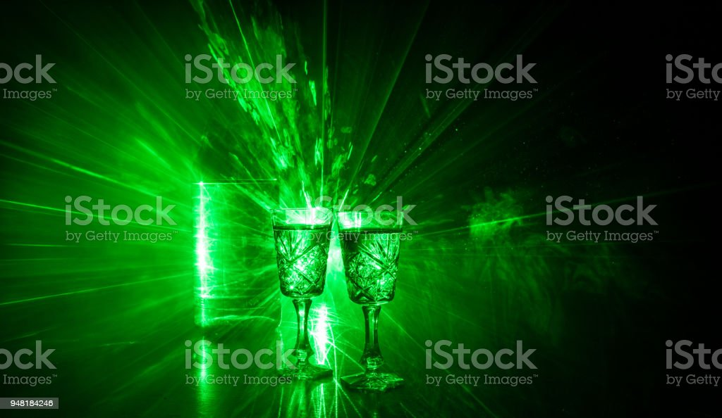 Two glasses of Vodka with bottle on dark foggy club style background with glowing lights (Laser, Stobe) Multi colored. Club drinks theme decoration. Empty space stock photo