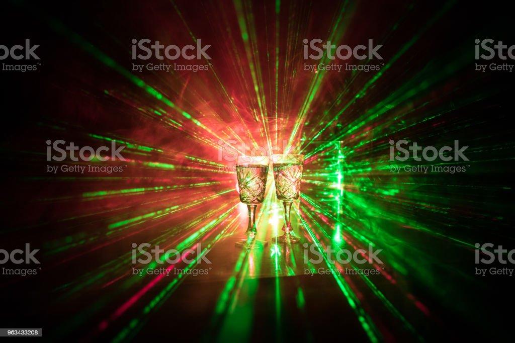 Två glas Vodka med flaska på mörka dimmigt club style bakgrund med glödande lampor (Laser, Stobe) Multi färgade. Club drinkar tema dekoration. Tomt utrymme - Royaltyfri Alkohol Bildbanksbilder