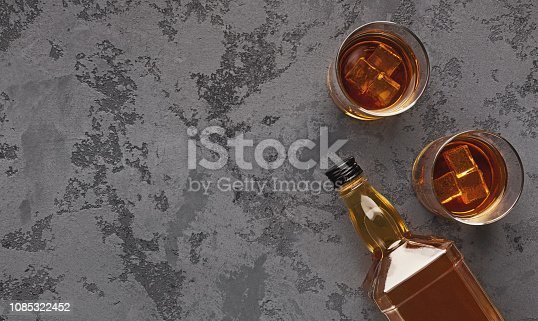 Two glasses of whiskey and bottle aside on marble background, top view, copy space