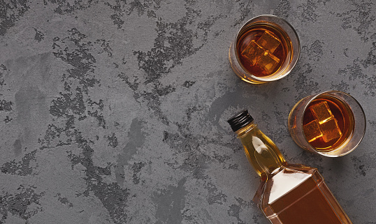 istock Two glasses of whiskey and bottle aside on marble background 1085322452