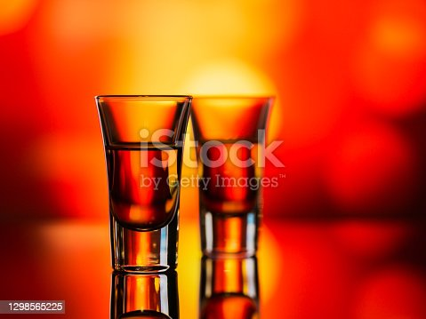 istock Two glasses of whiskey or bourbon on a red bokeh background. Whiskey mood concept 1298565225