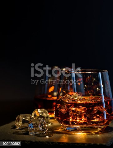 istock Two glasses of whiskey with ice on a black background 902420582