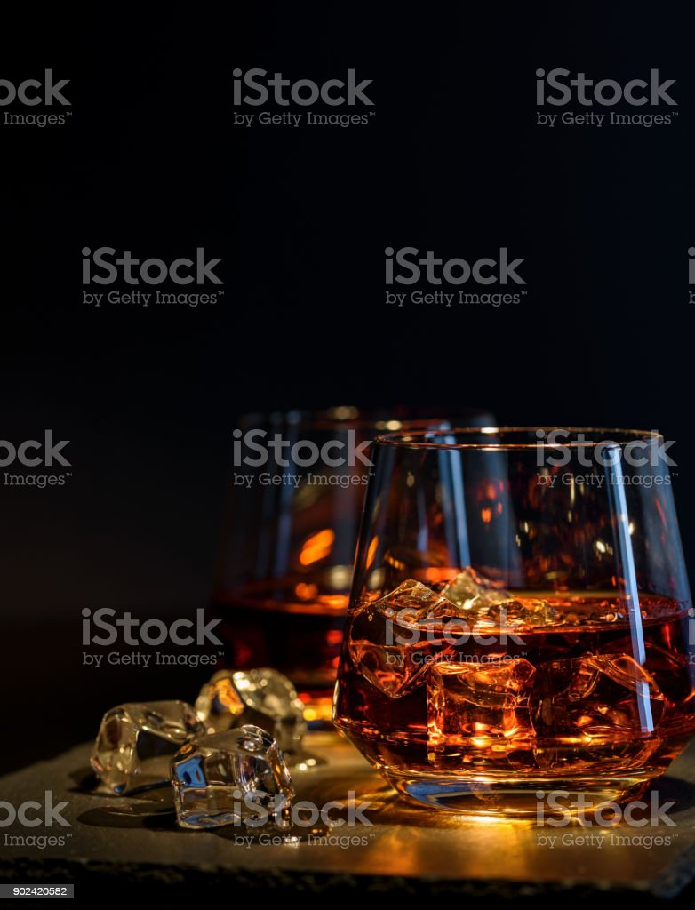 Two glasses of whiskey with ice on a black background stock photo