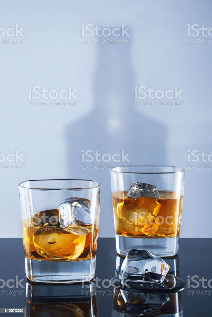 Two glasses of whisky and ice on a light background with a shadow from a bottle стоковое фото