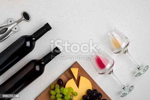 Two glasses of white and red wine, cheese and grapes. Two bottles of wine. Top view with copy space