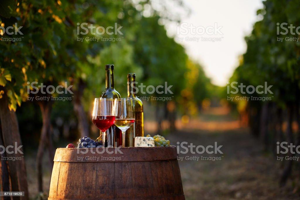 Zwei Gläser von weiß- und Rotwein mit Flaschen bei Sonnenuntergang. – Foto