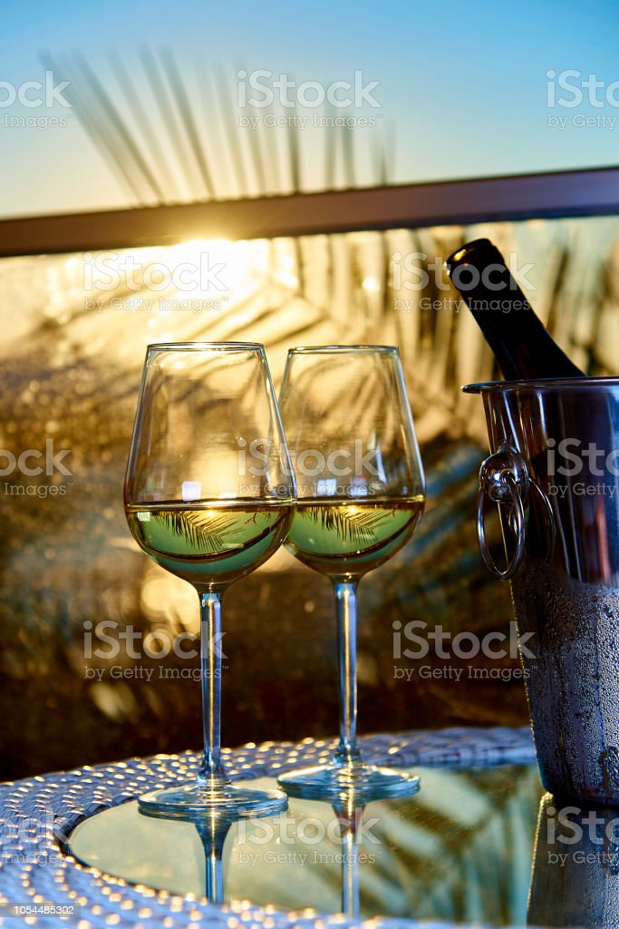 Two glasses of white cold wine on a glass table on the balcony in the...