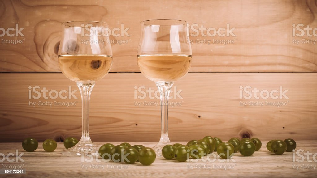 Two glasses of white wine and grapes on wooden table royalty-free stock photo