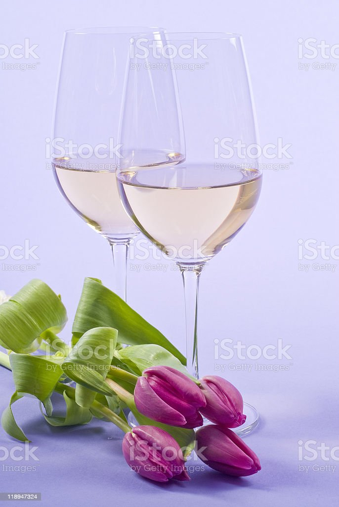 Two Glasses of White Wine and Pink Tulips stock photo