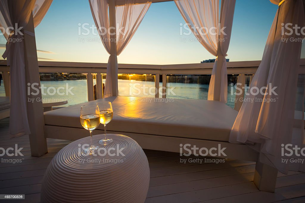Two glasses of white wine beside day bed at sunset. stock photo
