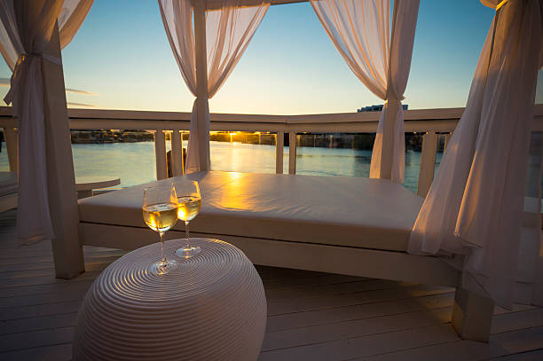 Two glasses of white wine beside day bed at sunset. Two glasses of white wine beside day bed at sunset. The day bed has curtains and is waterfront. There is condensation on the wine glasses and they look very refreshing. The sky is cloudless blue with the sun bright. Very romantic and relaxing scene. beach hut stock pictures, royalty-free photos & images