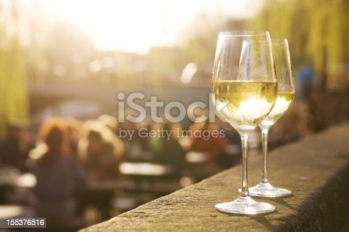 Two glasses of chardonnay on a sunlit cafe terrace, sunset light shining through the liquid.