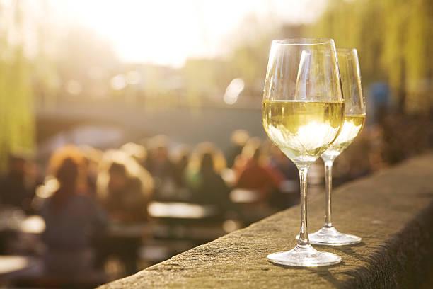 due bicchieri di vino bianco al tramonto - persona in secondo piano foto e immagini stock