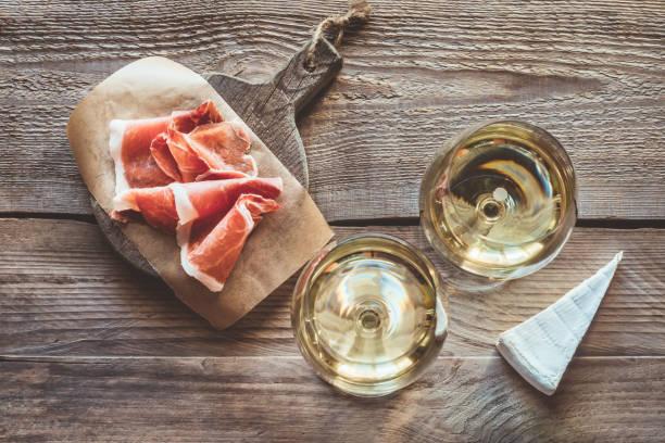 iki bardak beyaz şarap - parma jambonu stok fotoğraflar ve resimler