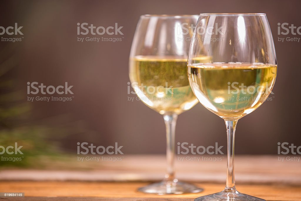 Two glasses of white wine. Rustic wooden table. Nobody. stock photo