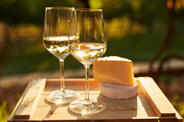 Two glasses of white wine with cheese Two glasses of white wine with cheese on wooden box, toned at sunset white wine stock pictures, royalty-free photos & images