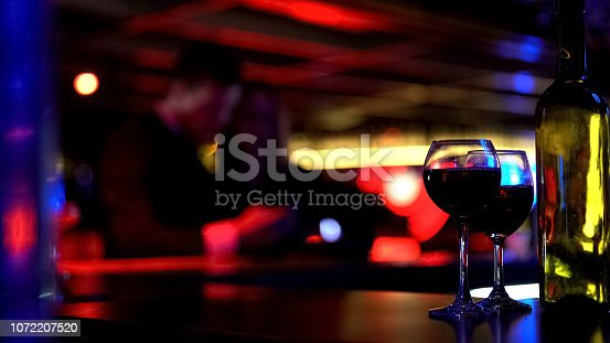 istock Two glasses of wine and bottle at bar in nightclub, couple on blurred background 1072207520