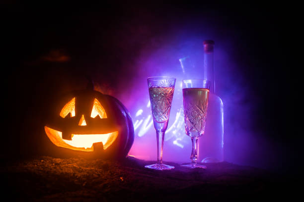 Two glasses of wine and bottle with Halloween - old jack-o-lantern on dark toned foggy background. Scary Halloween pumpkin – zdjęcie