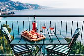 Two glasses of wine and italian snacks  with amazing view at sunset in Italy. Romantic dinner for two on panoramic terrace