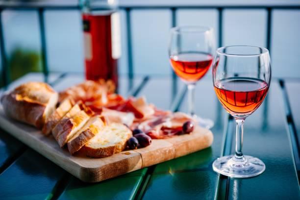 Zwei Gläser Wein und italienische Snacks mit herrlichem Blick auf den Sonnenuntergang in Italien. – Foto