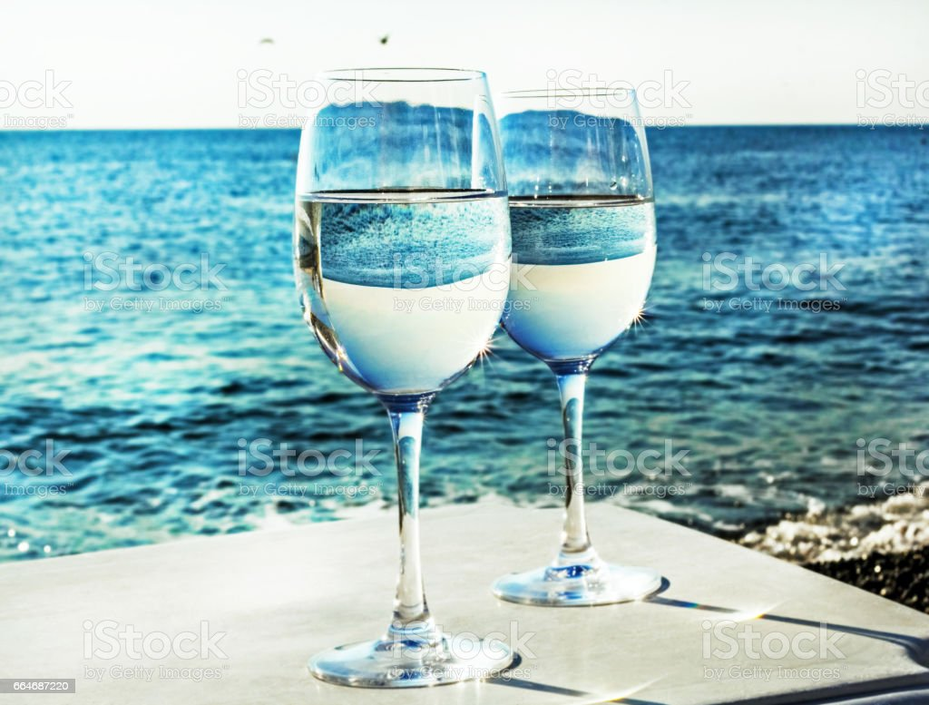 Two glasses of wine on beach stock photo