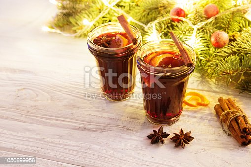 istock Two glasses of winter warming red hot drink Christmas mulled wine or tea on white wooden background table against christmas fir tree with christmas decorations and lights 1050699956