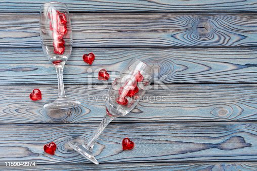 Two glasses, red figures in the shape of a heart on a wooden background. romantic date.
