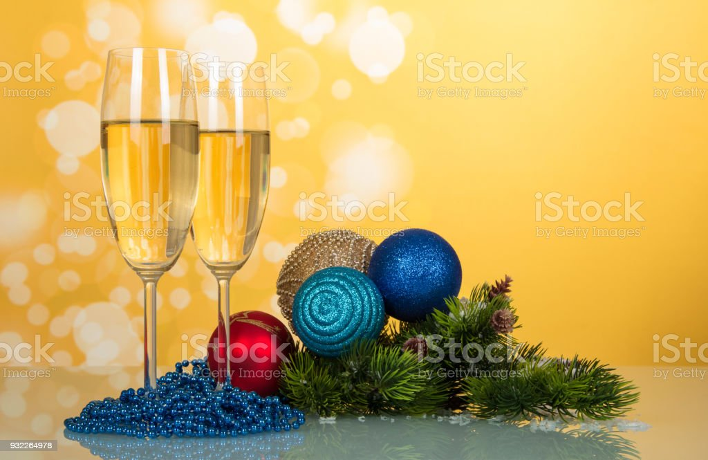 Two glasses with champagne, bright sparkling New Year's toys, pine branch and beads, on yellow background stock photo