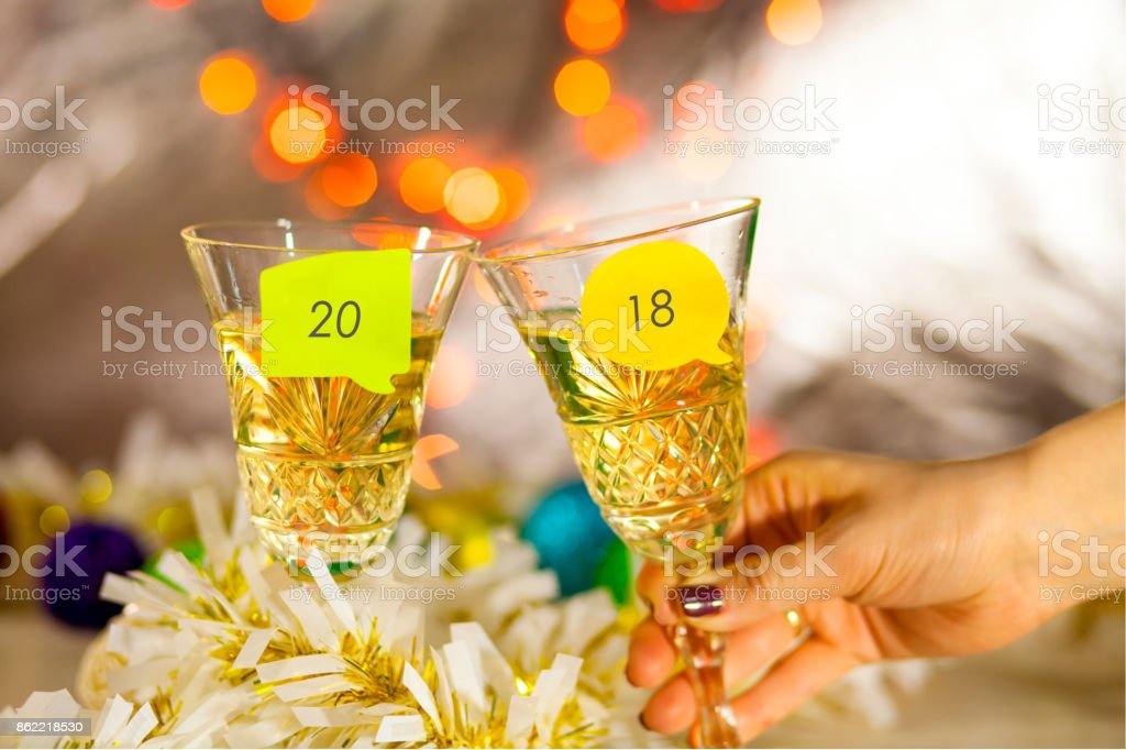 Two glasses with champagne on a table with stickers and an inscription 2018. New Year's bright blurred background stock photo