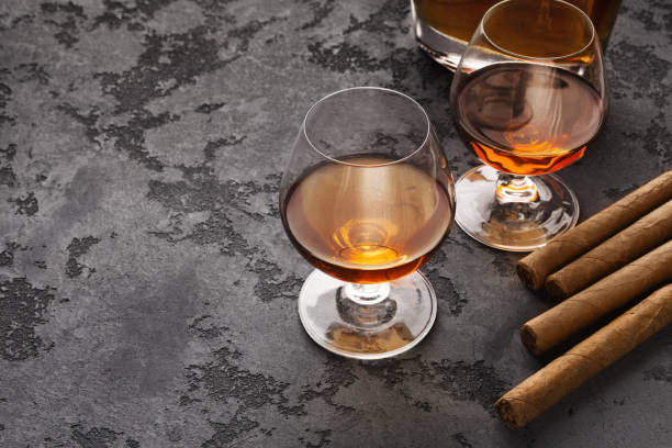 two glasses with cognac, bottle and cigars - stag night stock pictures, royalty-free photos & images