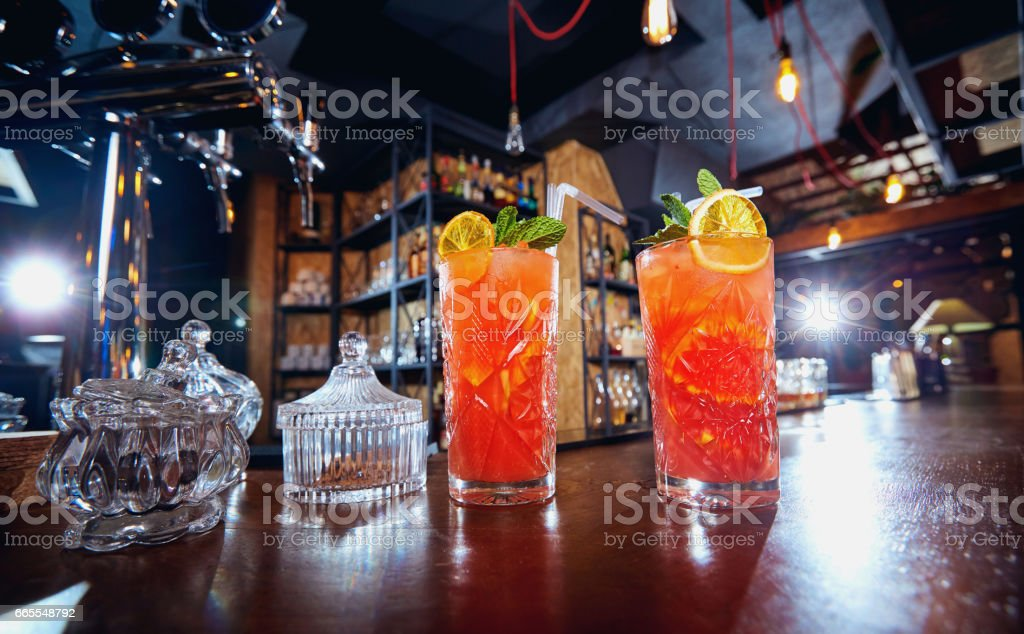 Two glasses with colored cocktails on the bar in restaurant stock photo