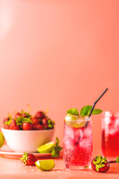 Two glasses with water drops of Strawberry mojito cocktail on soft pink color background. Copy space, summer vacation and party concept stock photo