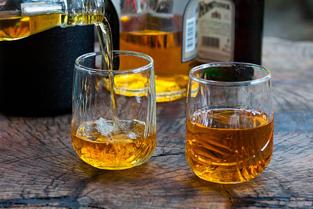 Two glasses with whiskey pouring in over a wooden table stock photo