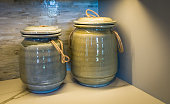 Two ceramic jars with a crackled glaze rest on a shelf in front of a tile wall