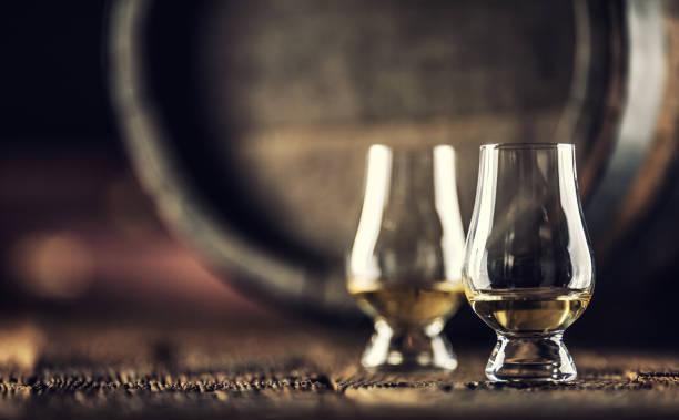Two Glencairn whisky tasting glasses on vintage wood and dark wooden barrel in the back stock photo