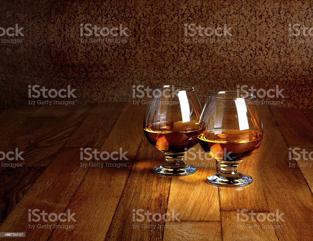 Two goblets of brandy on wooden old counter top stock photo