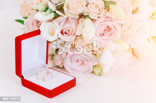 istock Two gold rings in red box near beautiful creame roses on white background 868159070