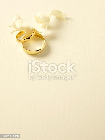 Two gold wedding rings tied with ribbon on textured paper with copy space.Click on the link below to see more of my wedding and party image.
