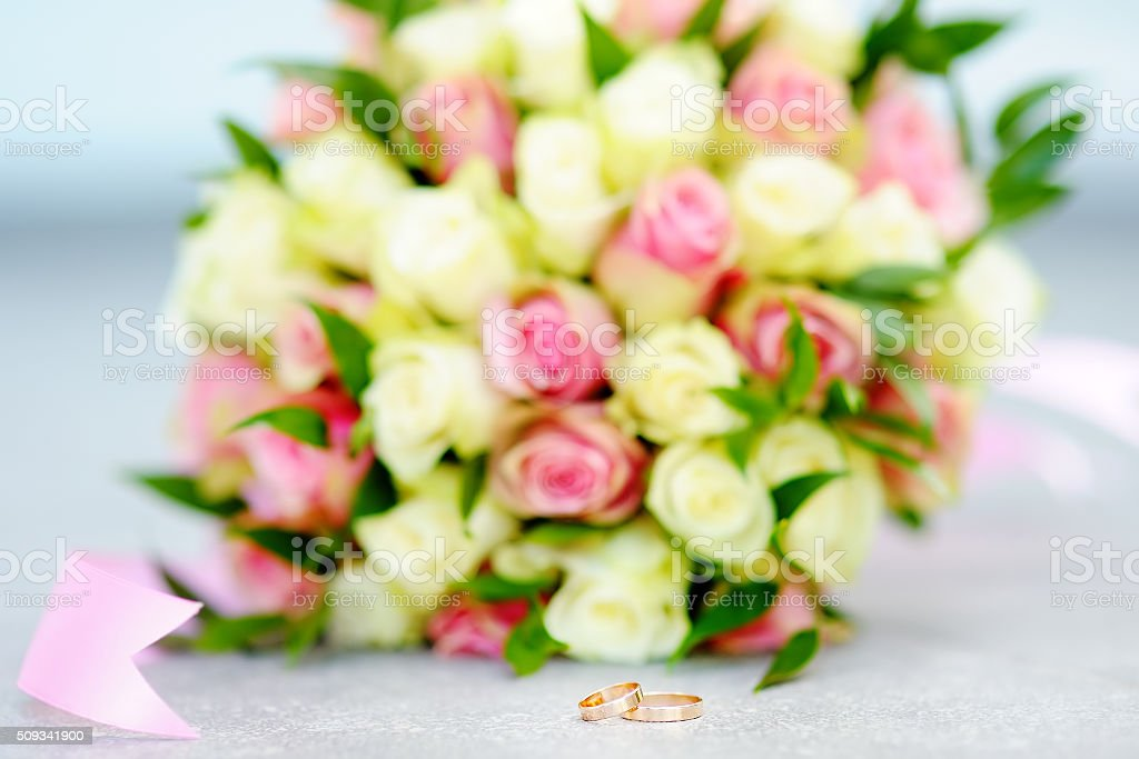 Two Gold Wedding Rings With Beautiful Flowers Bouquet On Background ...